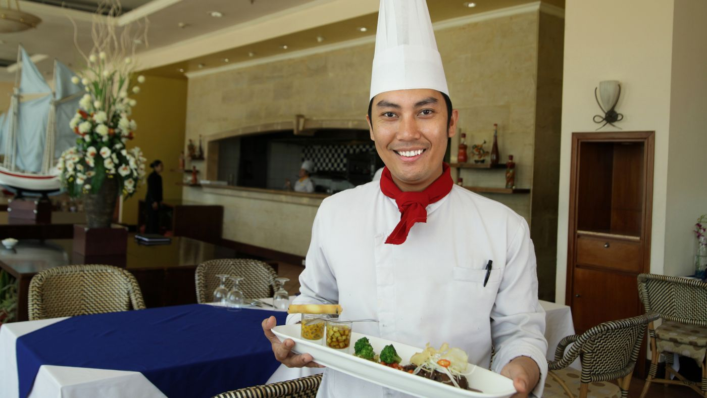 Happy young worker employed in a hotel kitchen carrying food