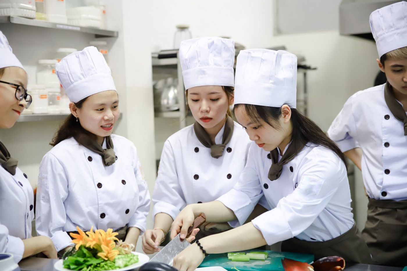 A group of young girls being trained on how to prepare food in a hotel kitchen.