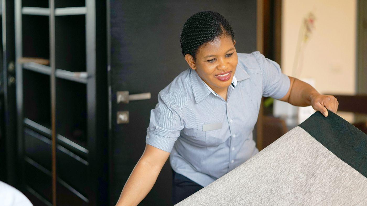 Hotel housekeeper making a bed