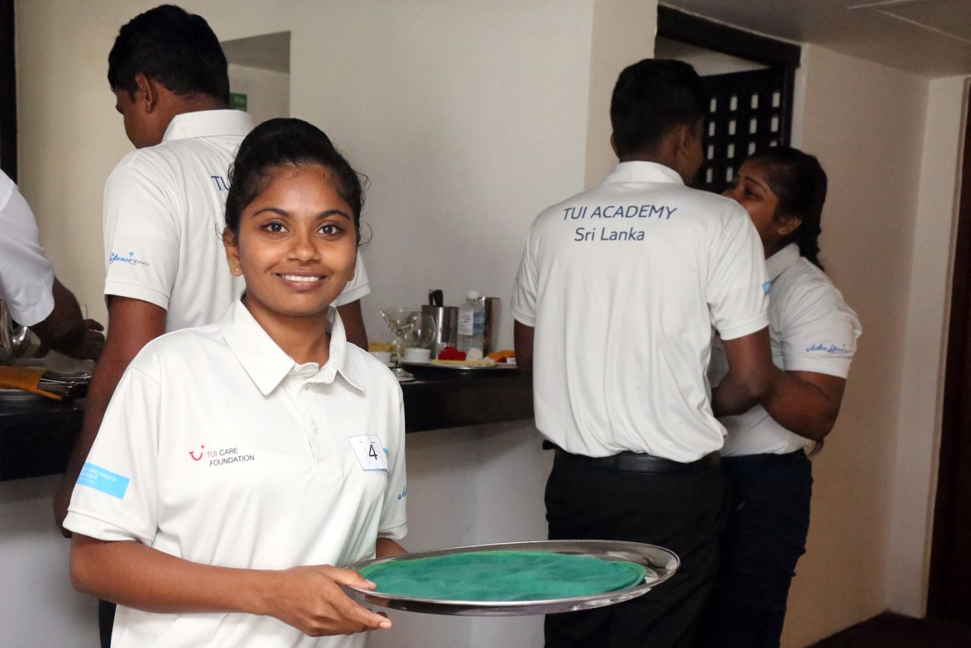 A young girl is holding a tray after serving drinks, as part of her hospitality training. She is a participant of our youth employment project, TUI Academy Sri Lanka, delivered in partnership with TUI Care Foundation.