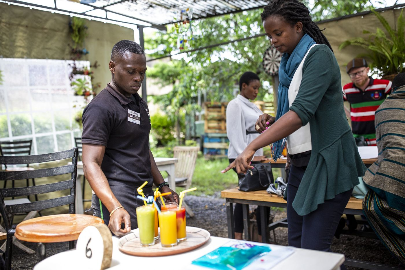 A young person is being trained on how to serve tables in a restaurant. He is a participant of Inclusive Futures, a six-year initiative funded by UK aid to promote disability inclusion in the workplace.