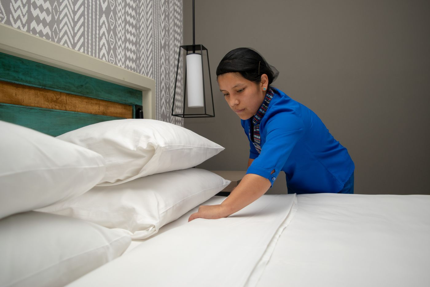 Young hotel housekeeper training how to make a bed. She is a participant of our youth employment programme in Latin America.