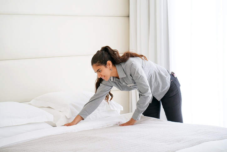 Trainee hotel housekeeper making a bed