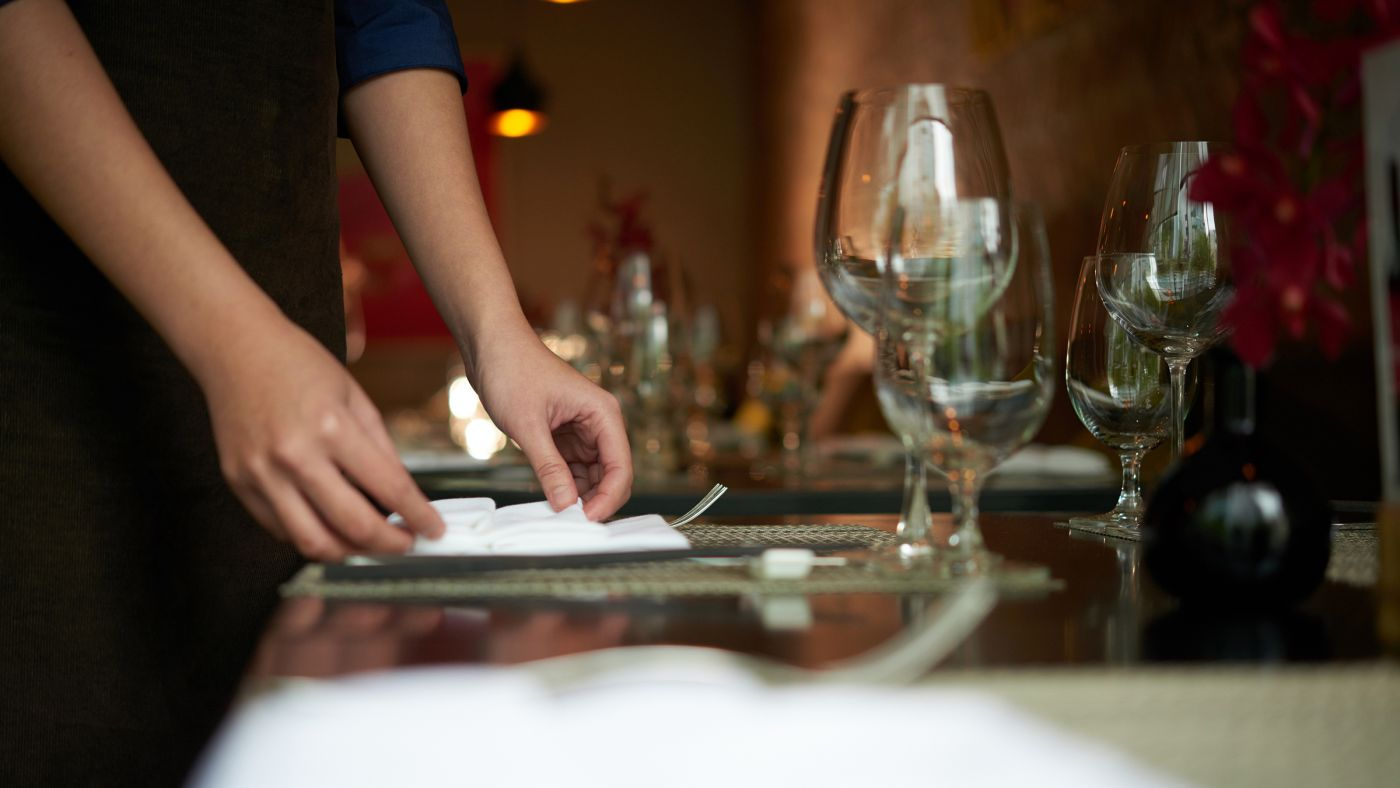 Hotel worker setting the table at restaurant