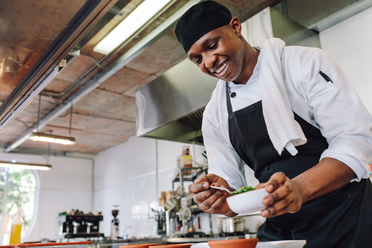 Happy young chef wearing apron preparing food in a hotel kitchen