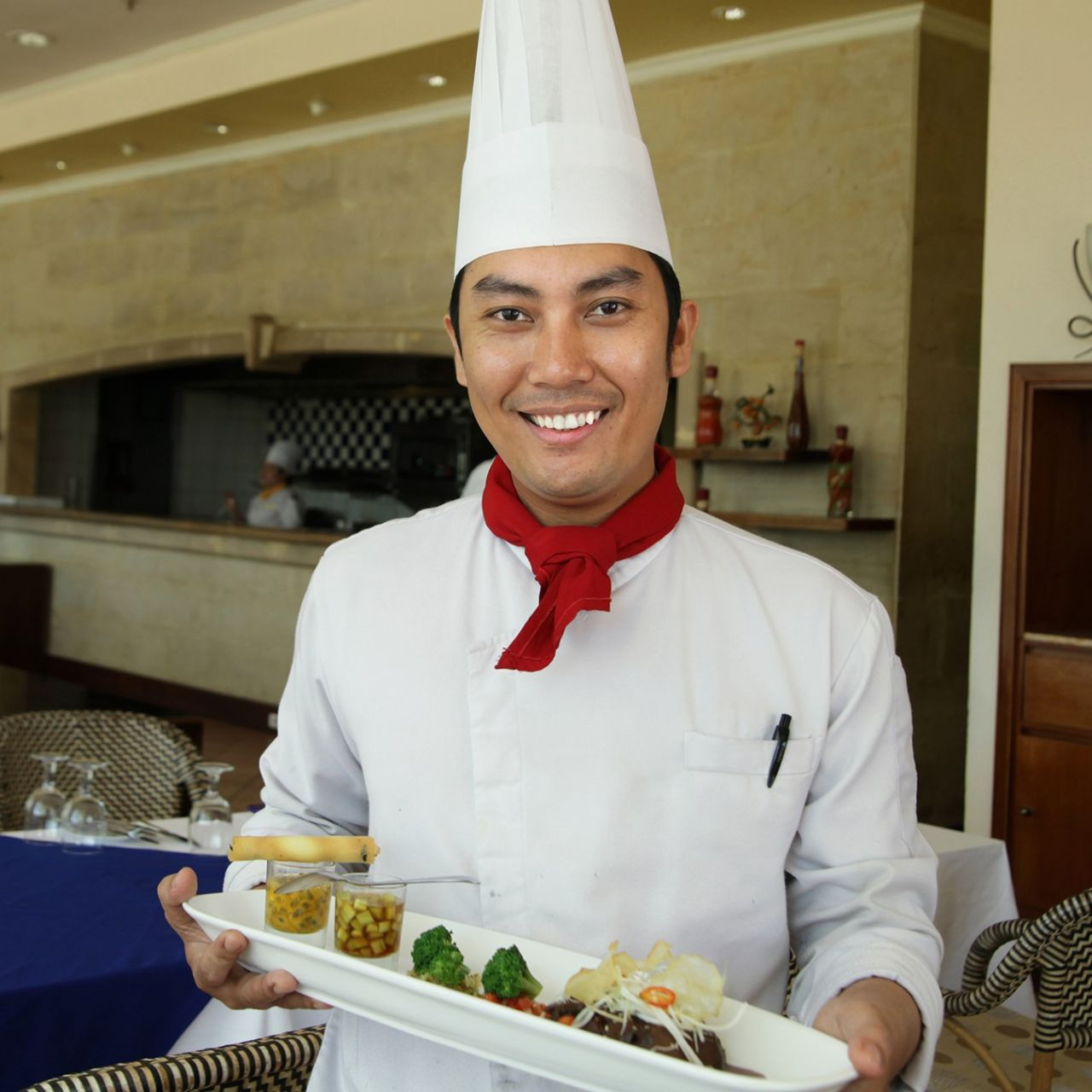 Young chef employed in a hotel holding some canapes